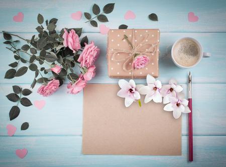 Rosa Rosen mit Blatt- und Magnolienblumen des leeren Papiers für Grußtext und Geschenkbox, Kaffeetasse auf Hintergrund von schäbigen hölzernen Planken. Kopieren Sie Platz. Ansicht von oben. Flaches Design. Standard-Bild - 85158049