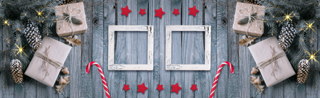 Christmas background with gift box and two empty photo frames in vintage style on wooden planks. New Year winter holidays concept. Empty place for photo. Copy space. Top view. Web banner.