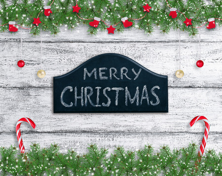 Christmas background in vintage style with balls, Santa boot and mitten hanging on spruce branches, signboard and New Year lollipops on wooden planks in Shabby Chic style.