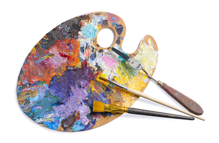 Wooden palette for oil paints with brushes and palette knife isolated on white background. Top view.
