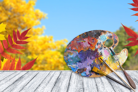 Palette for oil paints with brushes and palette knife on wooden table with autumn leaves against the blue sky