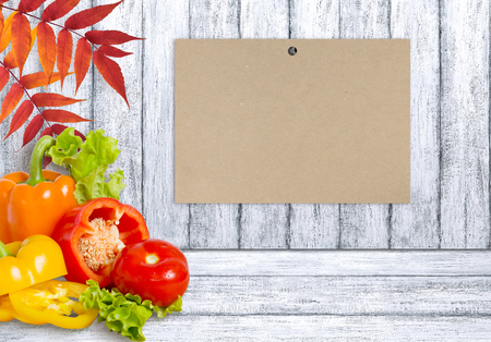 Ripe bell peppers, lettuce and tomato on wooden board and paper with place for text. Heap of various fresh bio vegetables. Healthy eating theme. Empty space for your advertising. Stock fotó