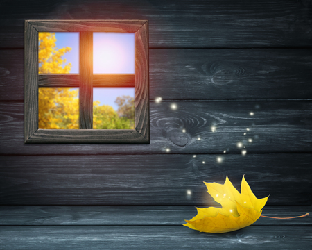 Room interior with window on dark wooden wall background and autumnal yellow maple leaf lying on table and shiny sparkles flying outside. Autumn sunny day. Empty space for your decoration.