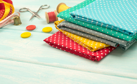 Workplace for seamstress. Set of reel of thread, centimeter, fabric, buttons, thimble and scissors for sewing and needlework on wooden surface Stock Photo