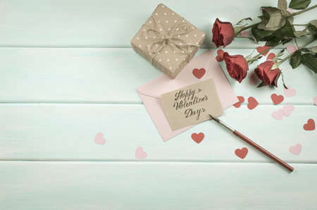 Valentine day theme. Top view of roses, hearts, packed gift and envelope on shabby wooden table.