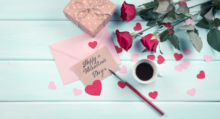 Valentine day theme. Top view of roses, hearts, packed gifts, coffee cup and envelope on shabby wooden table.  Stock Photo