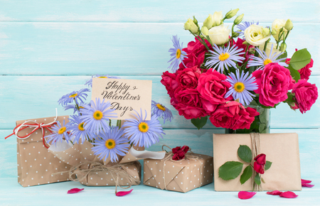 Valentine day theme. Roses and daisy bouquet, greeting card with gifts on wooden background in Shabby Chic style. Celebratory interior.