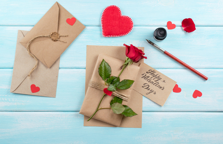 Valentine day theme. Top view of rose, hearts, greeting card, packed gift and envelope on shabby wooden table. Archivio Fotografico