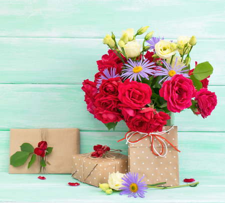 Roses bouquet with gifts on wooden background in Shabby Chic style. Celebratory interior. For this photo applied toning effect.