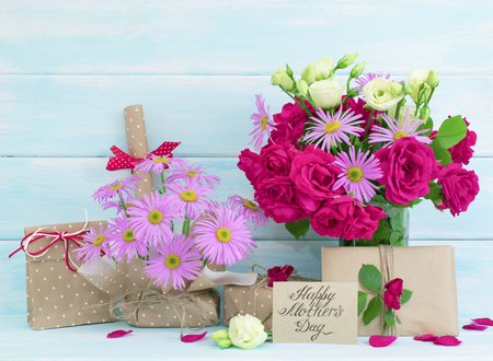 Mothers day theme. Roses and daisy bouquet, greeting card with gifts on wooden background in Shabby Chic style. Celebratory interior.