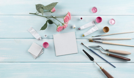 Workplace with miniature canvas, paintbrushes, palette knife, roses and paints on wooden boards. Top view. Flat  design. Stock Photo