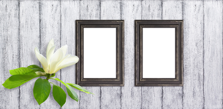Holiday background with pink magnolia flowers and two photo frame on wall of shabby wooden planks. Stock Photo