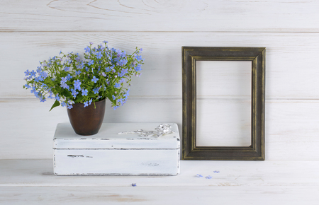 Forget-me-not flowers bouquet in clay cup, vintage casket and photo frame on white wooden shabby board in provence style Stok Fotoğraf