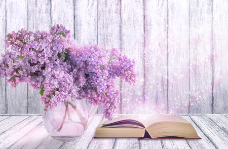 Room interior with lilac flowers in glass vase and open fairytale book on table in shabby chic style on wooden wall background with place for your decoration or text.