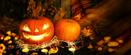 Autumn festive still life with evil smiling pumpkin on straw and leaves on background of wooden boards for Halloween