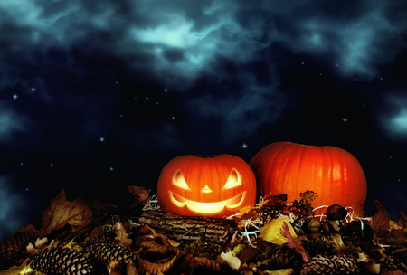 Autumn festive still life with evil smiling pumpkin on straw and leaves on background of cloudy sky with stars for Halloween