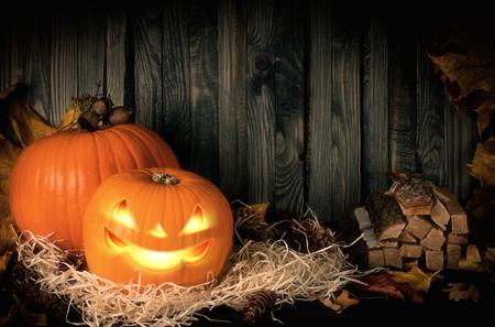 Jesienna świąteczna martwa natura ze złą uśmiechniętą dynią na słomie i liściach na tle drewnianej ściany na Halloween i miejsce na tekst