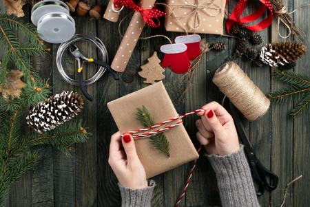 Christmas workshop theme. Top view of woman hands wrapping New Year present and tie bow. Packed gifts and scrolls, spruce branches and tools on shabby wooden table.