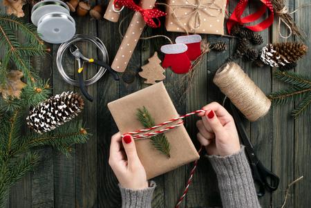thema kerstworkshop. Bovenaanzicht van vrouwenhanden die nieuwjaarscadeau inpakken en strik binden. Verpakte geschenken en rollen, sparren takken en gereedschap op armoedige houten tafel.