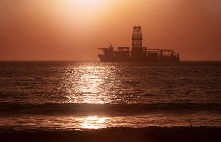 A large vessel on horizon in the atlantic ocean under the bright sun and red sunset. Sunlight reflection off the water