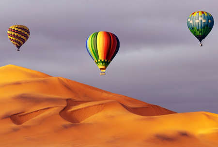 Beautiful Colorful Hot Air Baloons and dramatic clouds over the sand dunes in the Namib desert
