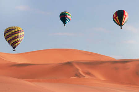 Colorful hot air balloons flying over sand dune seven, Walvis Bay, Namibia.