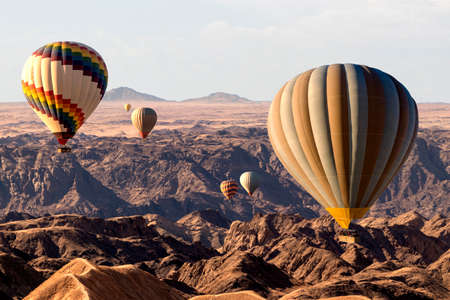 Colorful hot air balloons flying over the moon valley mountain. Africa. Namibia.