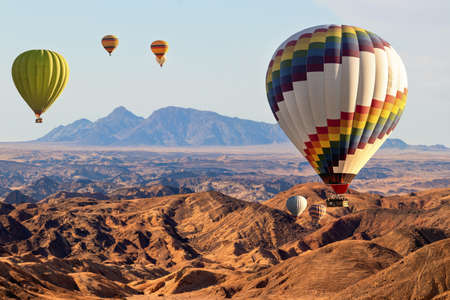Colorful balloons flying over the moon valley mountain. Africa. Namibia. Stock Photo