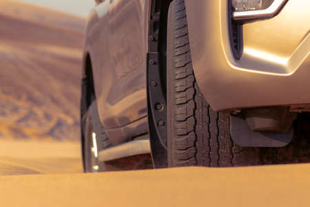 Close up of a golden car stuck in the sand in the Namib desert.