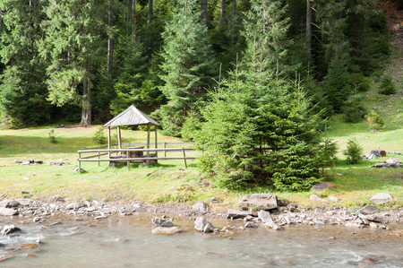 beautiful location: A wooden arbor near a mountain river in a beautiful location Stock Photo