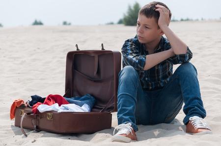 open suitcase: Upset teenage boy sitting on beach near open suitcase