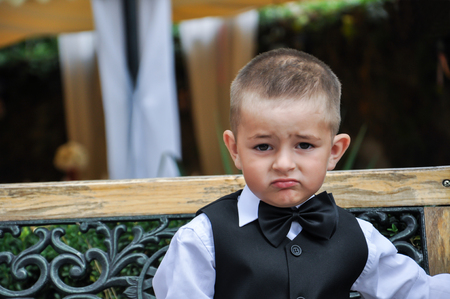 baby in suit: baby gentleman in a suit with a butterfly sitting on a bench