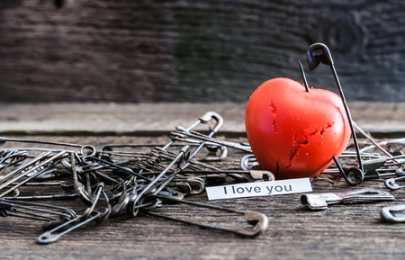 grieved: punctured red heart lots of sharp studs Stock Photo