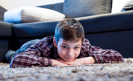 teen boy face: teenager with tablet while lying on the floor in the room Stock Photo