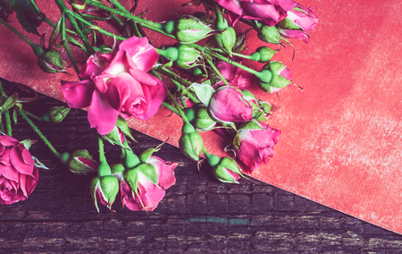 red sheet: small bouquet of pink roses on a red sheet of paper