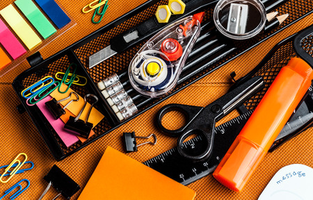 colorful school and office supplies on an orange background