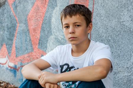 adolescente triste al aire libre cerca de un gris de las paredes
