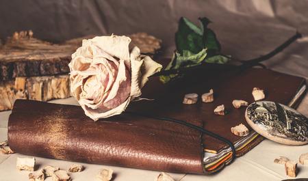 love letter: viejo cuaderno de cuero y una rosa secos sobre la mesa