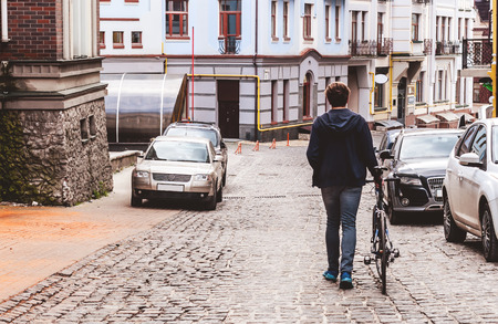 urban people: man with the bike goes on road from a stone