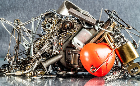 adhere: diverse iron pieces adhere to the magnet and red heart Stock Photo