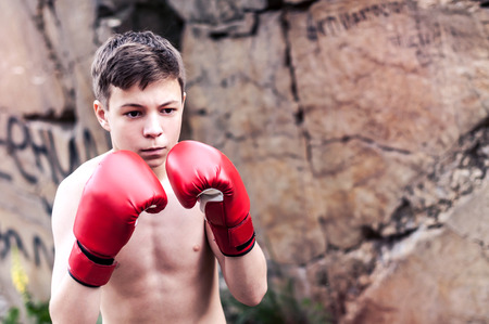young guy in boxing gloves near the cliff