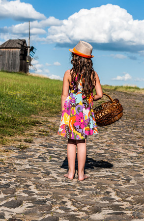 standing stone: little girl with a basket on the road from a stone Stock Photo