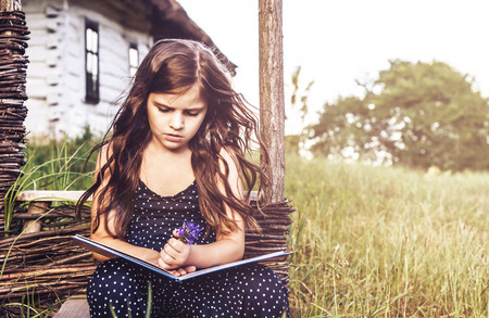 avocation: little girl reading an interesting book, sitting next to the house