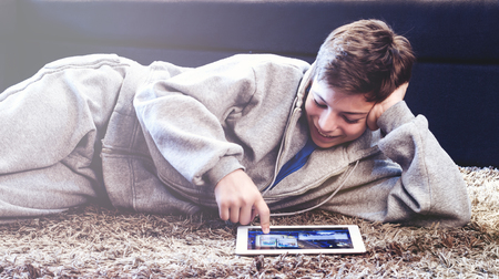 teenager with tablet while lying on the floor in the room Stock Photo
