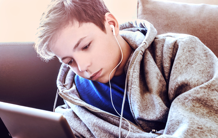 only one teenage boy: teenager with tablet while lying on the floor in the room Stock Photo