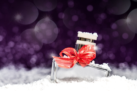 perfume bottle with a red bow in snow on a purple background