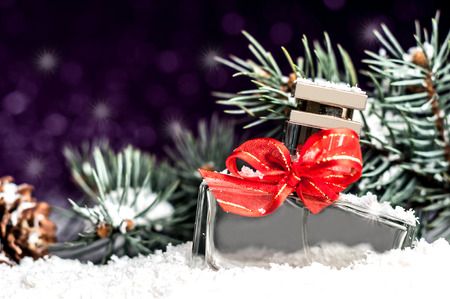 christmas perfume: perfume bottle with a red bow in snow on a purple background