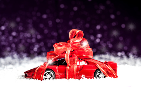 small car with red decorative bow in snow Reklamní fotografie