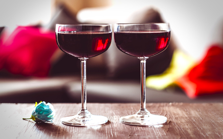 two glasses of red wine on a wooden table
