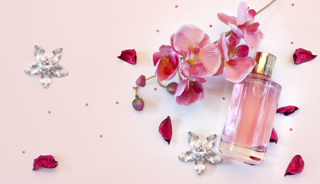 semitransparent: bottle of womens perfume and a delicate orchid flower on a pink background